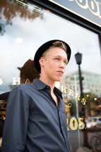 young man in a hat leaning against a restaurant window