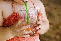 a toddler drinking from a straw