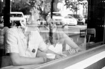 a couple sitting in a window of a coffee shop