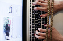 hands tied to a computer keyboard