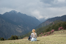 woman sitting on a slope looking out at mountains