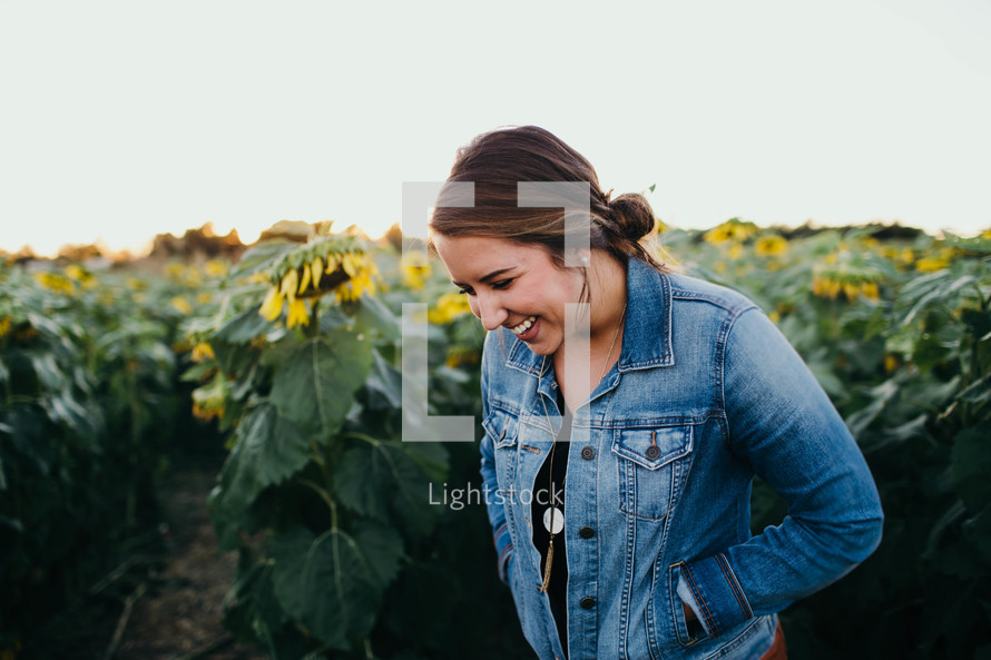 a woman laughing standing in a field of sunflowers