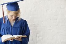 graduate reading a Bible