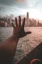 hand reaching towards a city over water