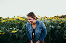 smiling young woman standing in a field of sunflowers