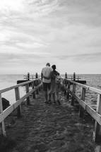 a couple walking down a pier