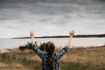 a woman with raised hands standing in front of a lake