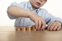 child stacking gold coins