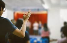 a person standing with hands raised at a worship service