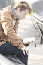 a man reading a Bible sitting on a bench