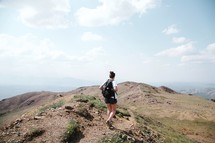 woman backpacking on a mountaintop