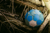 old soccer ball in a pile of sticks
