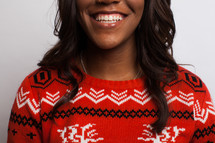 a smiling woman in a Christmas sweater
