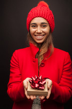 a woman in a red trench coat holding a gift box at Christmas