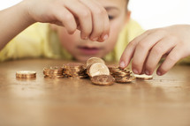 a boy child counting gold coins