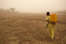 An Indian woman in yellow carries water on her back across a barren land.
