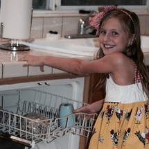 a little girl loading the dishwasher
