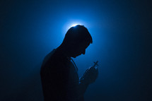 a man praying holding a cross illuminated in darkness