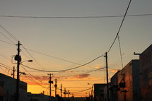 power poles and power lines against a sky at sunset