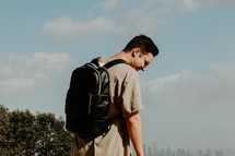 young man with a book bag and distant city view
