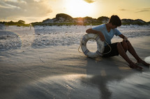 man sitting on a beach with a life preserver ring
