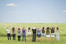 Women holding hands with arms raised in praise while standing in a field of grass.