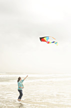 woman flying a kite at the beach