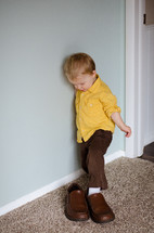 a toddler boy stepping into father's shoes