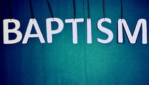 "Letters spelling the word, ""baptism,"" suspended from string."