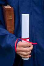 graduate holding a diploma and Bible