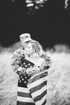 military couple wrapped in an American flag kissing