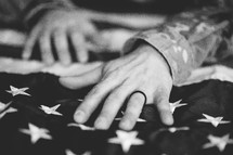 hands of a soldier on an American flag