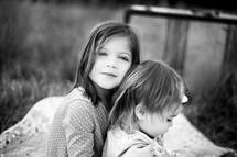 big sister and little sister hugging
