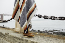a man wrapped in a blanket standing at the shore