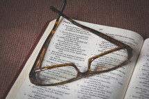Reading glasses on a Bible open to Psalm 139.