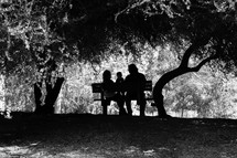 Man, woman and child sitting on a bench in a wooded area