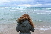A woman in a coat stands at the ocean's edge.