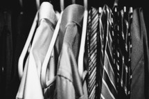 Shirts and ties hanging in closet.