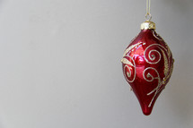 red and gold hanging Christmas ornament  agains white background