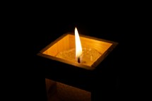 Lit votive candle in square wooden candle holder.