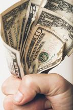 Fist grasping paper money.