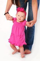 Mommy in jeans helping infant daughter in pink dress stand up and walk.