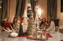 Christmas tree decorations on a table and women gathered in a living room