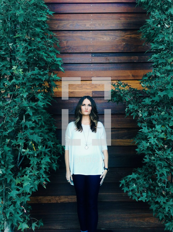 woman standing in front of a wall of wood
