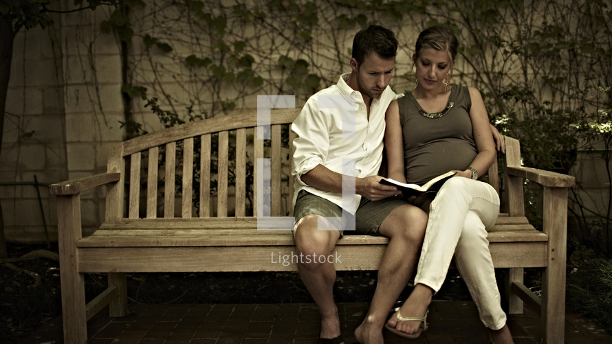 A man and woman reading the Bible on a bench.