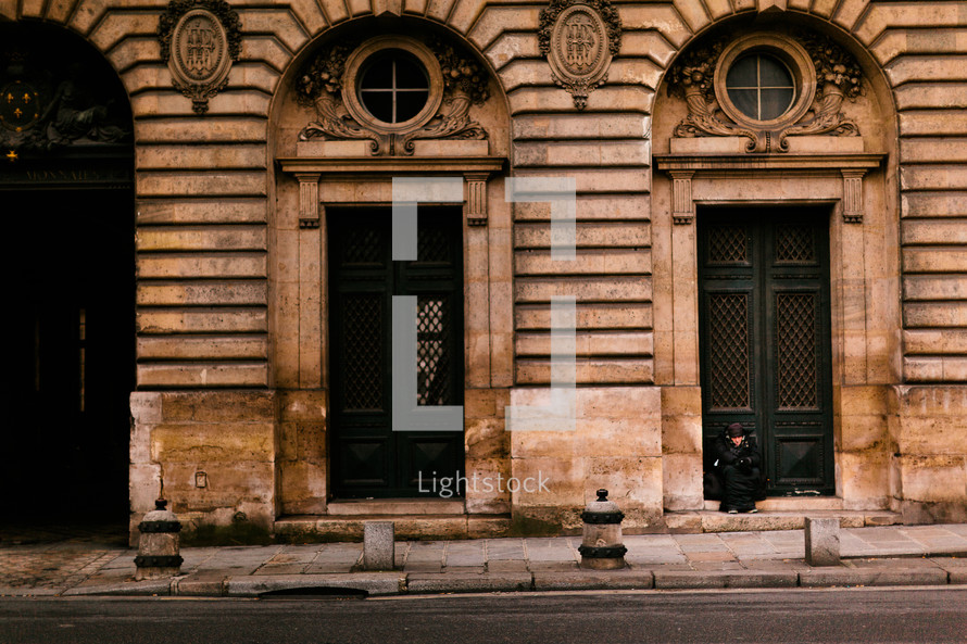 Man sitting in doorway - in front of old building - on a street