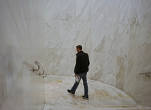 a man walking through a marble hallway