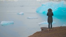 a woman in a coat looking out at icebergs