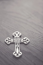 Silver cross on a wood table.