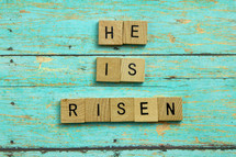 He is Risen on teal blue wood boards